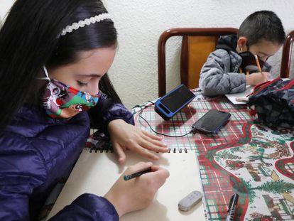Los estudiantes Isabela y su hermano Juan Diego Mora dibujan y escuchan el programa de radio Aprende en Casa de la Secretaría de Educación en Bogotá (Colombia).