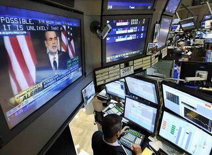 Una pantalla de televisión en la sala de operaciones de la Bolsa de Nueva York muestra la intervención de Ben Bernanke.