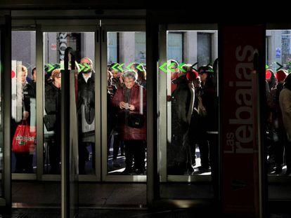 Un grupo de personas aguarda a la apertura de puertas de una tienda en Madrid.