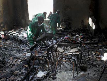 Dos operarios retiran escombros de la escuela de EE UU atacada el viernes.