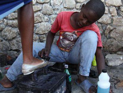 Un niño saca brillo a los zapatos de una mujer en Puerto Príncipe, Haití.
