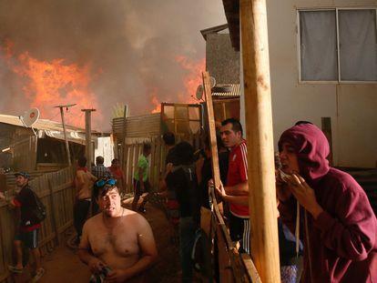 Al menos 6.000 personas han sido evacuadas a causa de un incendio registrado en los alrededores de la localidad chilena de Viña del Mar, en la región de Valparaíso (Chile). En la imagen, algunos residentes de Viña del Mar trabajan para evitar que el fuego se extienda a sus casas.
