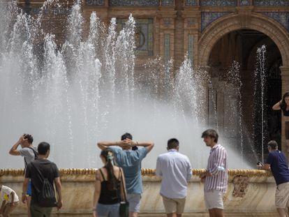 Varios jóvenes se refrescan en la fuente de la plaza de España en Sevilla, este martes.