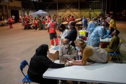 Una trabajadora del Gobierno da la bienvenida a una familia evacuada. En segundo plano, los sanitarios realizan pruebas PCR a los que han viajado en el avión, este jueves en Torrejón de Ardoz.