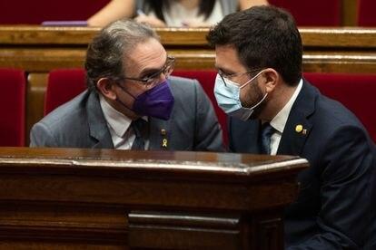 A la derecha, el presidente catalán, Pere Aragonès, conversa con el conseller de Economía y Hacienda, Jaume Giro, durante el pleno del Parlament este jueves.