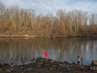 Niños migrantes observan Grecia desde la orilla turca del río Evros, frontera natural entre ambos países, en marzo de 2020.