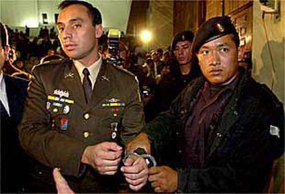 La policía militar escolta al capitán Byron Oliva, uno de los cuatro condenados, en los juzgados de Guatemala.