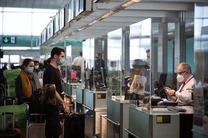 Viajeros en un mostrador de equipajes en la terminal 1 del aeropuerto de Barcelona en diciembre de 2020.