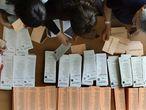 Varios electores cogen ayer papeletas en un colegio electoral.