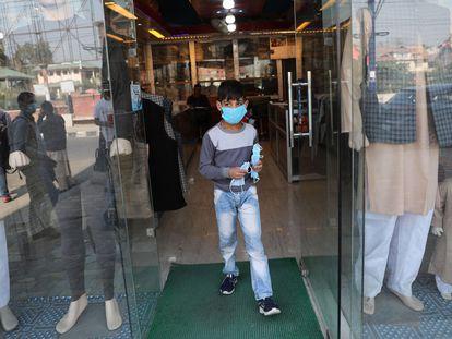 Un niño de Cachemira sale de una tienda después de distribuir mascarillas para prevenir la propagación del coronavirus, en Srinagar, la capital de verano de la Cachemira india.