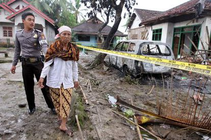 Un policía acompaña a Aminah, madre de uno de los muertos en el linchamiento del domingo, a su casa destruida en Pandeglang.