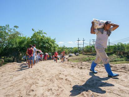 Un hombre carga una bolsa de ayuda humanitaria cerca de Coloma, Honduras.