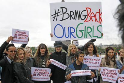 Actrices y modelos francesas posan frente a la Torre Eiffel con pancartas para mostrar su apoyo a la liberación de las niñas secuestradas en Nigeria.