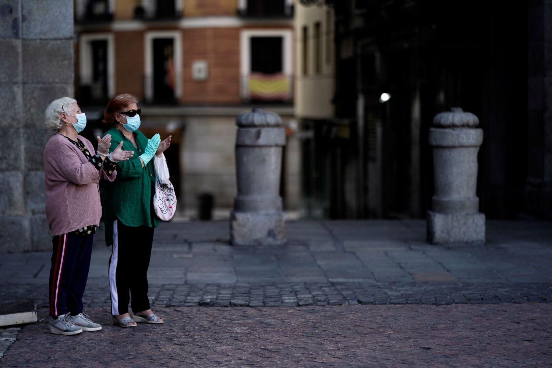 Dos mujeres, en la Plaza Mayor de Madrid, aplauden en homenaje al personal sanitario el 3 de mayo.