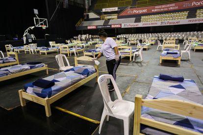 Una mujer desinfecta una cama habilitada para mayores de 65 años que serán alojados en el Palacio Peñarol en Montevideo, el 27 de marzo.