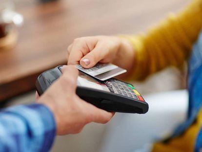 Una persona realiza un pago con una tarjeta.