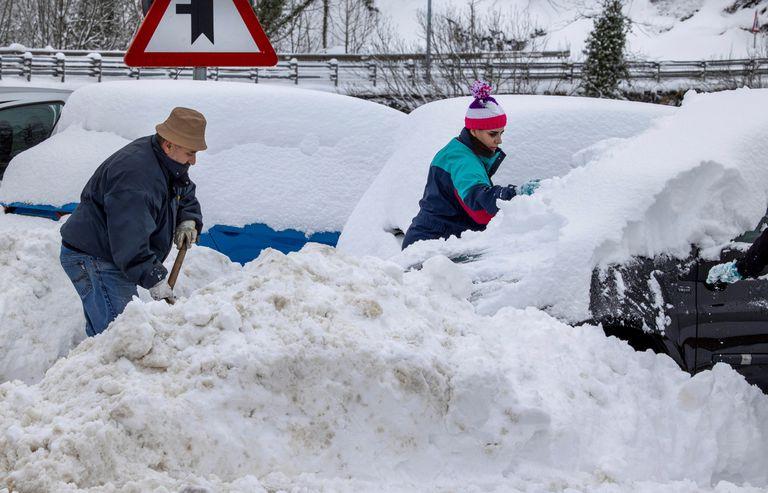 Unos vecinas tratan de quitar la nieve de sus vehiculos en el pueblo de Pajares, a principios de esta semana.