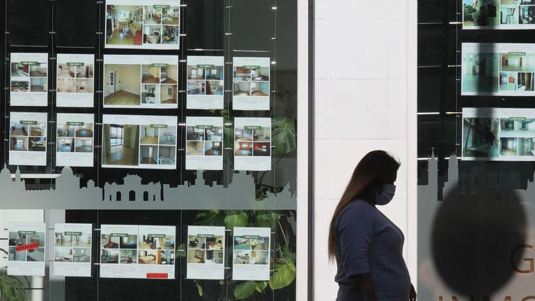 Una mujer pasa delante de una agencia inmobiliaria de Madrid.