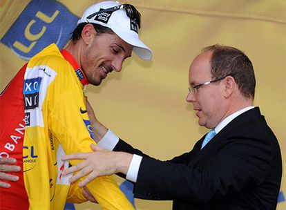El Príncipe Alberto de Mónaco viste a Fabian Cancellara con el 'maillot' amarillo.
