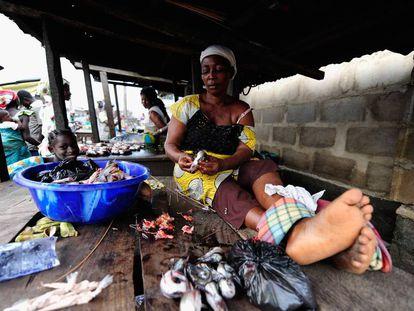 Una mujer limpia pescado en un mercado en Nigeria.