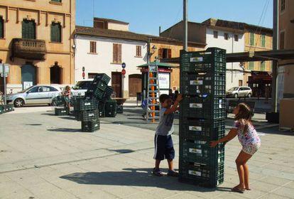 Un niño y una niña juegan con cajas de sandía en Campos, Mallorca, en agosto de 2014. / Arquitectives