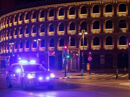 Un coche de policia circula junto a la plaza de toros de Valencia durante la medianoche de este sábado.