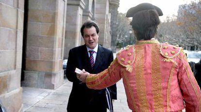 Artur Mas recibe una octavilla de un partidario protaurino disfrazado de torero a la salida, ayer, del Parlamento de Cataluña.