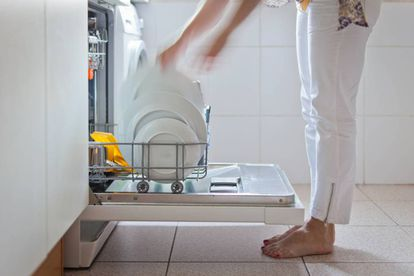 A woman removes the dishes from the dishwasher.  GETTY