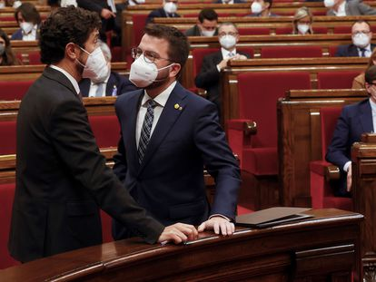 El 'president' en funciones, Pere Aragonès, a la derecha, conversa con el titular de Territorio, Damià Calvet, antes de comenzar el pleno del Parlament.