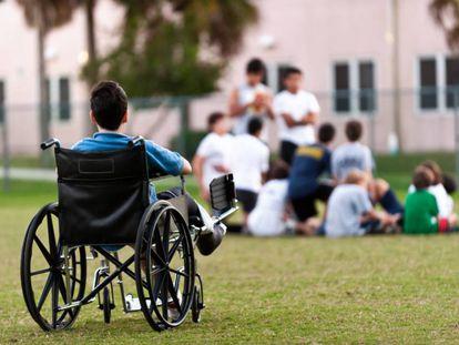 Un adolescente en silla de ruedas observa a sus compañeros jugando en el parque mientras le excluyen.