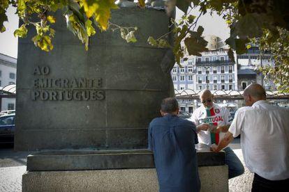 Un grupo de taxistas juegan a las cartas al lado de la estatua dedicada al emigrante portugués.