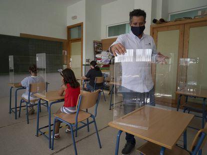 Varias niñas prueban las mamparas de seguridad instaladas en las mesas de un aula del colegio 'Carmen Borrego' en la localidad sevillana de El Rubio, financiadas con el dinero de las fiestas municipales.