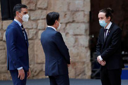 El presidente español, Pedro Sánchez (izquierda), y el presidente italiano, Giuseppe Conte (centro), saludan al vicepresidente  Pablo Iglesias, durante la recepción en el patio de honor del palacio de la Almudaina, en el que se celebra la XIX Cumbre Bilateral de España e Italia, este miércoles en Palma de Mallorca.