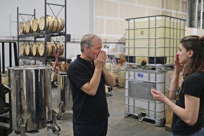 Dos trabajadores huelen un desinfectante de manos producido en una una destilería reconvertida en Fairfield (EE UU).