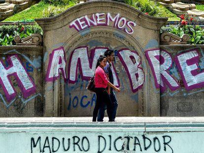 Una pareja pasea frente a un grafiti de protesta contra el Gobierno venezolano.