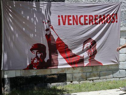 Un hombre camina junto a una tela adornada con una imagen del líder de la revolución cubana Fidel Castro en La Habana (Cuba).