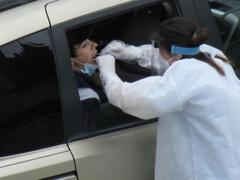 Una trabajadora del Hospital de Eibar realiza el test PCR al conductor de un vehículo en el parking del centro.