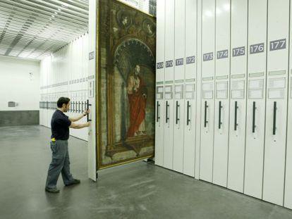 Un operario extrae un peine con obras de arte en los depósitos del edificio Jerónimos del Prado.