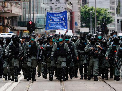 Un grupo de policías antidisturbios en Hong Kong camina durante una marcha de protesta contra la nueva ley de Seguridad Nacional