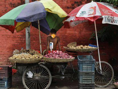 Un vendedor de verduras usa una mascarilla protectora mientras espera a los clientes en Kolkata, India, el 17 de julio de 2020.