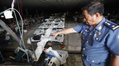 Un policía señala el punto donde se produjo el derrumbe de una de las plantas de una empresa textil de Camboya.