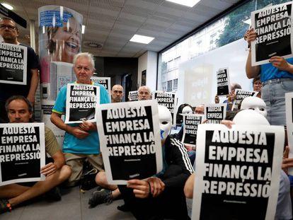 Activistas sentados en una sucursal de Caixabank en Gràcia. En vídeo, las imágenes de la ocupación,
