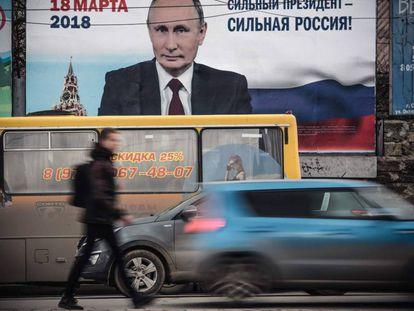 """Un hombre pasa delante de un afiche electoral en favor de la candidatura del presidente de Rusia, Vladímir Putin, """"¡Un presidente fuerte, una Rusia fuerte!"""", en Crimea."""