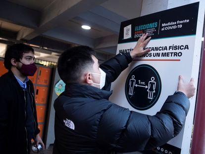 Dos trabajadores del Servicio Electoral de Chile (Servel) instalan carteles orientativos para los votantes en el Colegio Providencia, uno de los centros habilitados para las elecciones del 15 y el 16 de mayo.