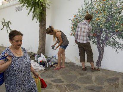 La artista Ona Juskiene realiza un mural en la calle Álamos de Genaguacil.