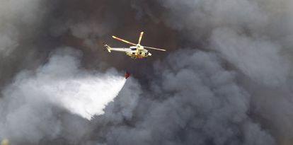 Un helicóptero sobrevuela las áreas quemadas.