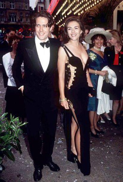 Liz Hurley con el famoso vestido negro de Versace junto a Hugh Grant, en el estreno de 'Cuatro bodas y un funeral'.
