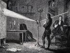 Isaac Newton con el prisma para descomponer la luz blanca en el espectro. Lo acompaña su compañero de habitación de Cambridge John Wickins. Grabado de 1874.