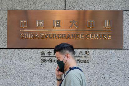 Hombre pasa por la sede de Evergrande en Hong Kong el lunes