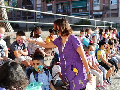 Una maestra toma la temperatura el primer día de colegio en la escuela Rafael Casanova de Badalona.